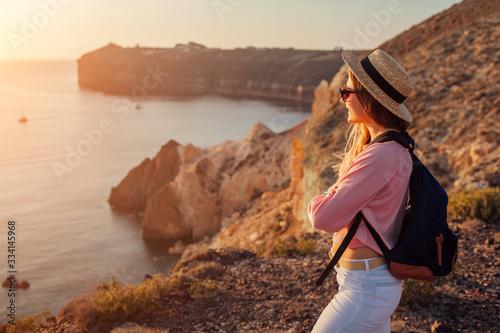 Obraz Traveler hiking by White beach on Aegean sea Santorini island, Greece enjoying landscape. Woman backpacker on vacation - fototapety do salonu