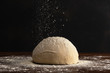 canvas print picture - Pastry chef sprinkles flour on fresh raw dough for bread or pizza on a dark background.