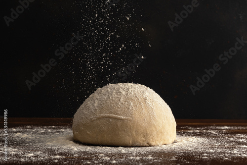 Pastry chef sprinkles flour on fresh raw dough for bread or pizza on a dark background Fototapeta