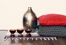 Cozy Home Interior Decor, Burning Spa Aroma Candles In Coconut Shell On A Multi-colored Rug, Near Metal Vase And Decorative Pillows .