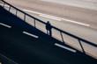 Mann steht auf einer Brücke mit seinem Schatten