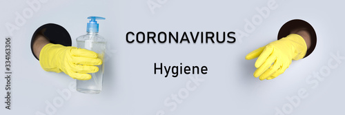 Obraz Hands in yellow gloves hold an antiseptic gel for hygiene through paper hole. Coronavirus prevention protective. Banner with text: Coronavirus. Concept. Safe shopping. - fototapety do salonu