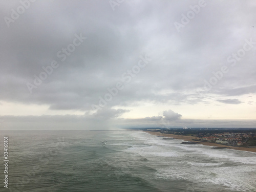 Photo View of a shore, agitated ocean and cloudy sky