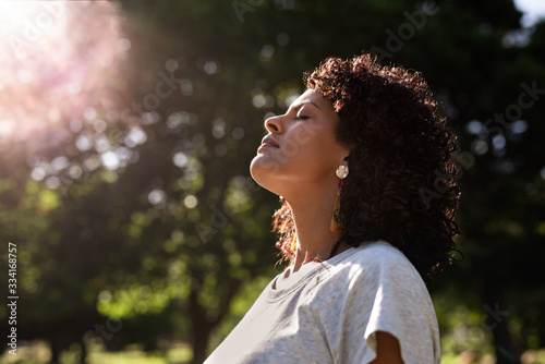 Fototapeta Young woman standing outdoors feeling the sun on her face