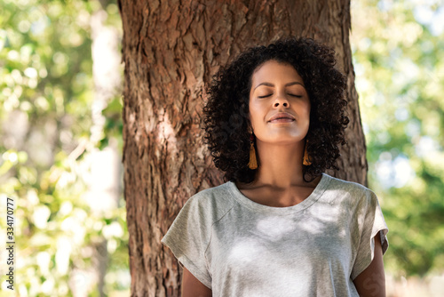 Cuadros en Lienzo Peaceful woman leaning against a tree with her eyes closed