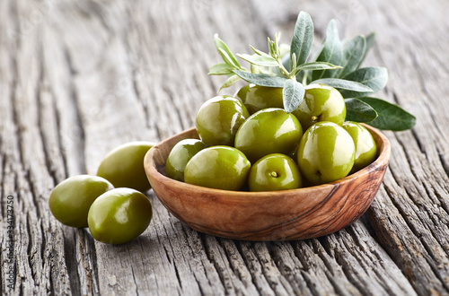 Fényképezés Green olives with leaves on wooden background