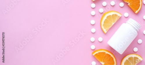 Fototapeta scattered vitamin pills and bottle with lemon orange on pink background. Copyspace, flat lay, banner. Concept boost immune system, medicine and tablets. obraz