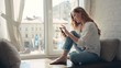 Charming young woman sitting on a windowsill at home and texting on her phone communication female looking message cellphone cheerful smile use internet modern smartphone