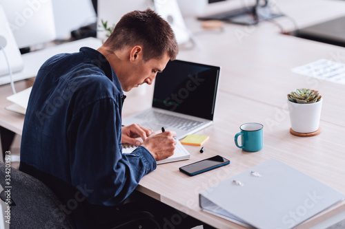 Businessman wearing blue shirt sitting in the office at the desk and writing not Tapéta, Fotótapéta