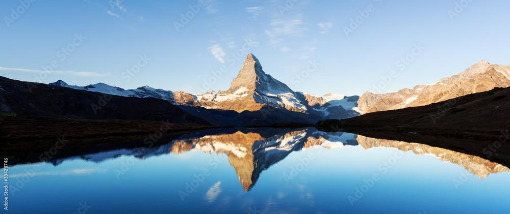 Fototapeta Picturesque landscape with colorful sunrise on Stellisee lake. Snowy Matterhorn Cervino peak with reflection in clear water. Zermatt, Swiss Alps