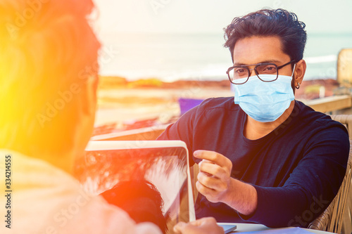 Photo handsome indian man wearing mask and talking with worker colleague