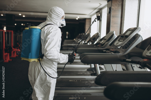 Obraz Cleaning and Disinfection in crowded places amid the coronavirus epidemic Gym cleaning and disinfection Infection prevention and control of epidemic. Protective suit and mask and spray bag - fototapety do salonu