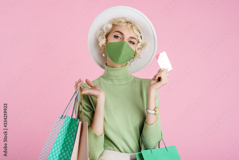 Fototapeta Spring online shopping during quarantine conception: fashionable woman wearing protective mask posing with colorful paper bags and plastic bank card. Pink background. Copy, empty space for text