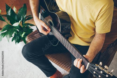 Tela Close-up of a man holding a guitar and learning guitar chords for beginners