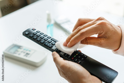 Fotografía Woman hand cleaning TV remote controller with disinfectant wet wipe and alcohol in living room at home