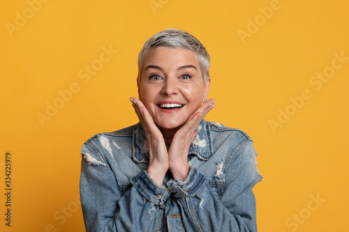 Portrait Of Surprised Middle Aged Woman Touching Her Cheeks In Excitement Fototapeta