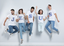 Group Of Young People Wearing T-shirts With Letters Near Light Wall. Christian Religion