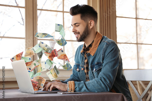 Fototapeta Man with modern laptop and flying euro banknotes at table indoors. People make money online obraz