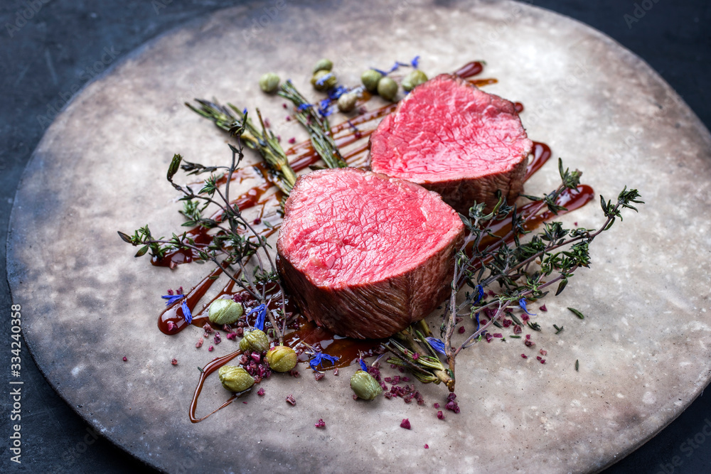 Fototapeta Gegrilltes dry aged Rinderfilet Medaillon Steak natur gebratenen Kräuter und Kapern als closeup auf einem Modern Design Teller