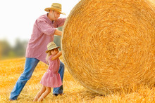 Father With A Child Play Kittens A Haystack On The Field. Happy Family Work Hard At The Ranch.