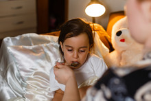 Sick Little Girl In Bed Taking...