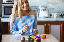 Holidays, Handmade And Creation Concept - Happy Young Woman Draws On Easter Egg.