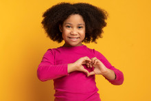 Adorable Little African American Girl Showing Heart Gesture With Hands