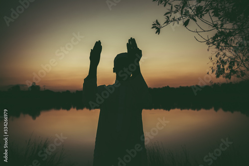 Photo Silhouette Young asian muslim man praying on sunset,Ramadan festival concept