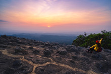 Tourists Sit With Arms And Watch The Sunset Over The Rocky Line At Phu Hin Rong Kla National Park, Phitsanulok Province.
