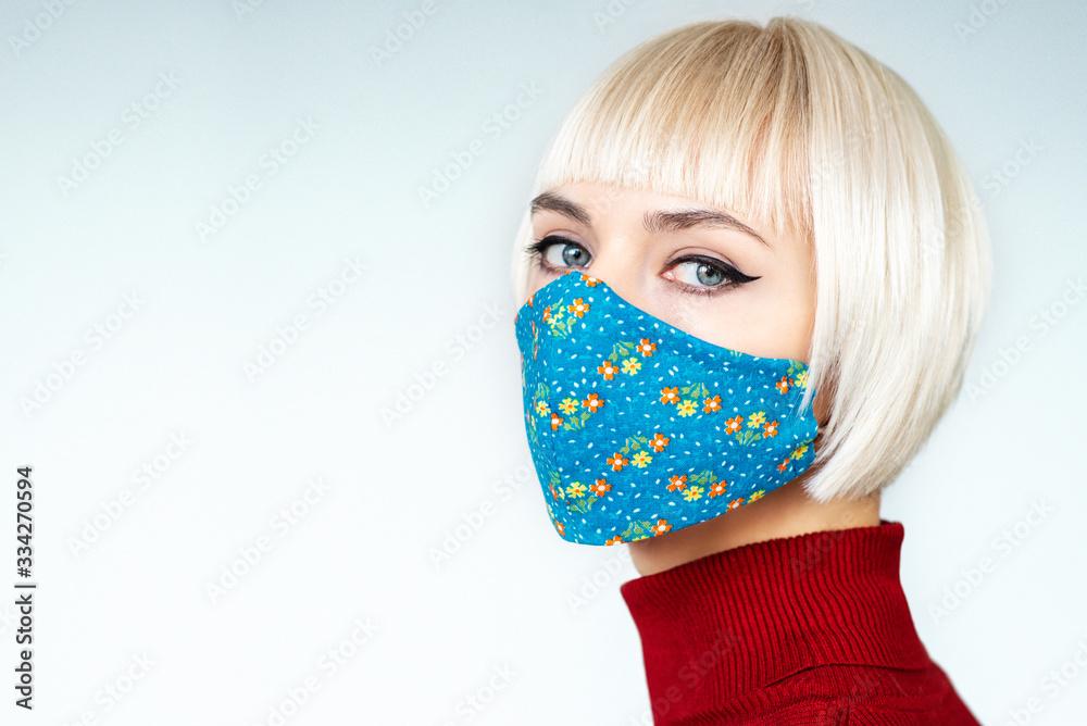 Fototapeta Woman wearing stylish handmade protective face mask. Fashion during quarantine of coronavirus outbreak. Copy, empty space for text