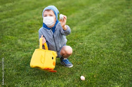 Fototapeta Little boy wearing protective mask hunting for Easter egg in spring garden. obraz