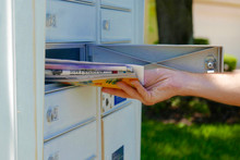 A Hand Is Pulling A Pile Of Mail Out Of A Mailbox