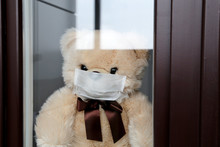 Toy Bear In A Face Medical Mask Looks Out Of The Window. Concept Of Coronavirus Quarantine During The COVID-19 Epidemic
