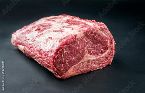 Canvastavla Raw dry aged wagyu entrecote beef steak roast as closeup on a black background w