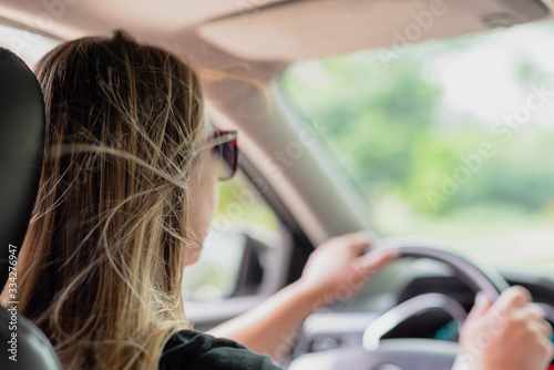 Foto Over the shoulder view of attractive young woman driving on a summer day