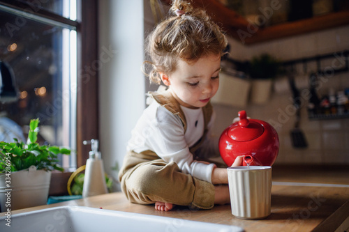 Stampa su Tela Cute small toddler girl sitting on kitchen counter indoors at home, pouring tea