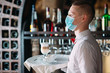 canvas print picture - A European-looking waiter in a medical mask serves Latte coffee.