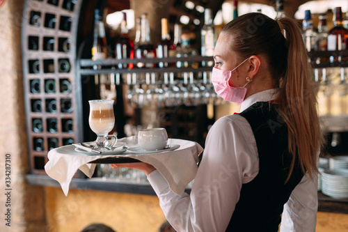 Fototapeta A female Waiter of European appearance in a medical mask serves Latte coffee