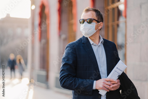 Obraz Working in pandemic situation. Business worker or entrepreneur wears medical mask for coronavirus protection stands beside office building outdoor holds newspapers concentrated somewhere into distance - fototapety do salonu
