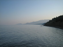 Rocky Coast At Sunset. In The Distance, The Coast Mountains Loomed In The Mist.