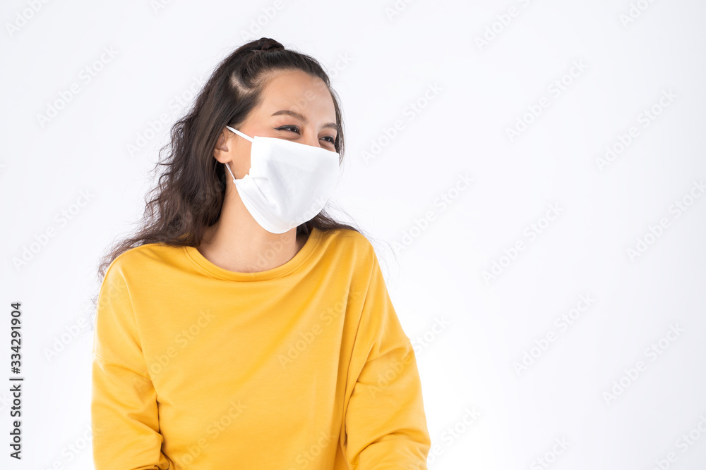 Fototapeta Young happy Asian woman wearing hygienic mask to prevent infection corona virus Air pollution pm2.5 she wearing a yellow sweater shoot in shot isolated on white background