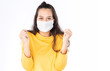 Leinwandbild Motiv Young happy Asian woman wearing hygienic mask to prevent infection corona virus Air pollution pm2.5 she wearing a yellow sweater shoot in shot isolated on white background
