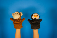 Soft Puppet Toys On Hands On Blue Background. Concept Of Puppet Show. Close-up Of Hands With Puppet Monkey And Penguin.
