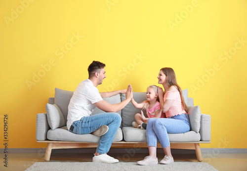 Happy young family playing while sitting on sofa near color wall Tableau sur Toile