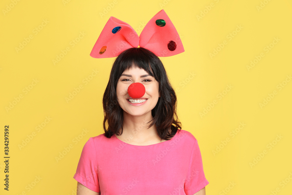 Obraz Joyful woman with large bow and clown nose on yellow background. April fool's day fototapeta, plakat