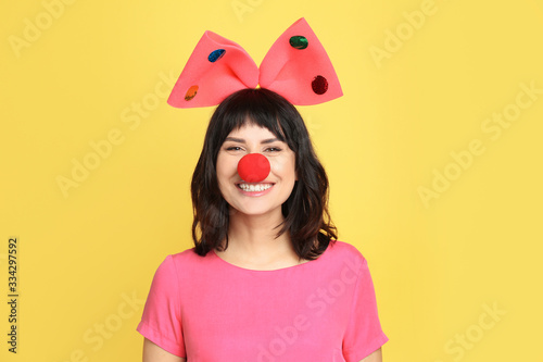 Fototapeta Joyful woman with large bow and clown nose on yellow background. April fool's day obraz