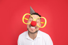 Funny Man With Large Glasses, Party Hat And Clown Nose On Red Background. April Fool's Day