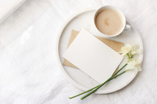 Breakfast In Bed Mockup Scene Near Window. Cup Of Coffe, Greeting Card, Narcissus, Daffodil Flowers On Marble Tray. White Linen Table Cloth Background. Spring, Easter Concept. Flat Lay, Top View.