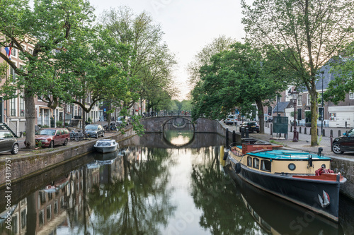 Amsterdam canal with boats and a bridge Canvas Print