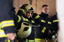 Professional Firefighters Wearing Uniforms. Firewoman Putting On Protective Helmet.
